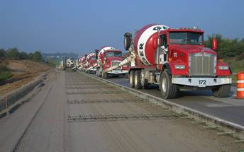 Concrete trucks pouring road
